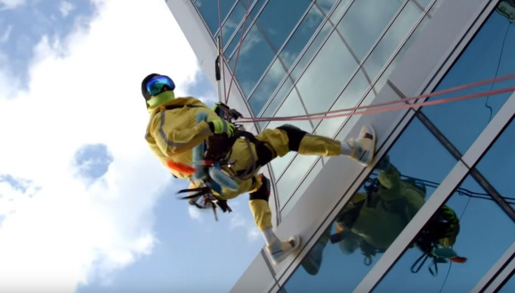 Man repelling down exterior of building